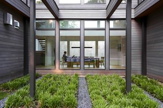 Ten-foot windows frame views of a Zen garden built along the exterior in front of the home.