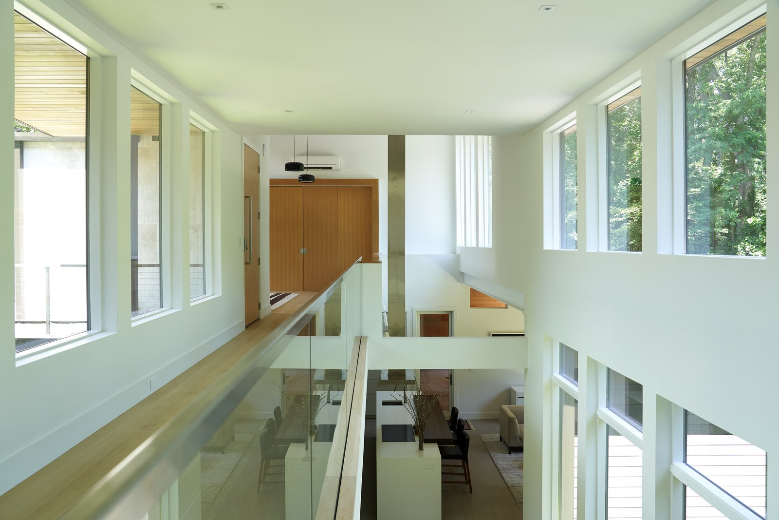 Windows, Metal, Wood, and Picture Window Type The master bedroom and a lofted child's room are situated on opposite ends of the home, linked together by a catwalk that overlooks the main lower living areas.  Photo 7 of 9 in Walls of Windows Connect a Home With Earth and Sky