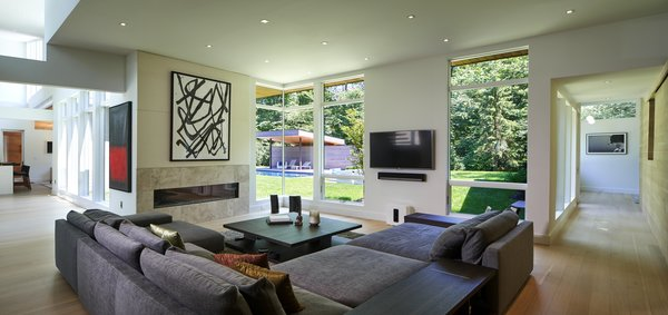 A corner window unit in the living room offers a full view of the  swimming pool, with narrow sight lines and a slim corner post. Additional windows wrap around both sides of the room.