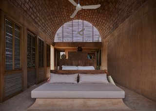 Inside the bedrooms, exposed bricks create a striking atmosphere underneath the barrel-vaulted ceiling. A latticework of reed encloses the roof, allowing for easy circulation of fresh, warm air throughout the space.
