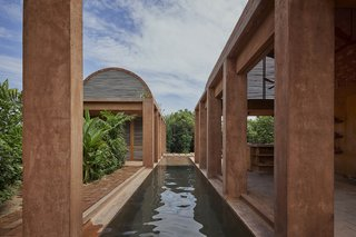 A long, narrow reflecting pool divides the rectilinear structures. Stained concrete pillars blend with clay-colored bricks, given their particular shade from prior use during the clay firing process at a local art studio.