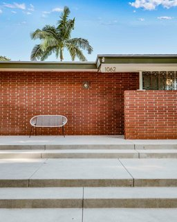 A modest brick exterior hides the home's unique interior design. The flat roof and clean lines are the only cues to the midcentury modern compound that awaits.