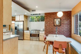 The updated kitchen features custom maple and plywood cabinets built to resemble the original space. An exposed brick wall and triangular backsplash tiles further accent the modern design.