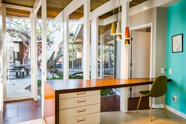 From this angle, the hallway emerges as a canopy of thin wooden frames. A built-in desk faces the glass wall and patio, providing visual separation for the bedroom.