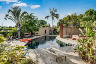 The resort-like backyard features a solar-heated pool surrounded by a large flagstone patio. Closer to the house, a more intimate garden area includes a mosaic-tiled outdoor shower.