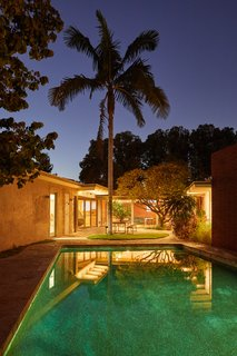 The backyard patio and pool glow in the moonlight, recalling a feeling of glory days from the retro Googie era.