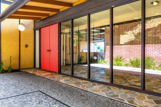 """The home features a classic midcentury color palette. Warm earth tones are paired with o<span style=""""font-family: Theinhardt, -apple-system, BlinkMacSystemFont, &quot;Segoe UI&quot;, Roboto, Oxygen-Sans, Ubuntu, Cantarell, &quot;Helvetica Neue&quot;, sans-serif;"""">chre-tinted</span><span style=""""font-family: Theinhardt, -apple-system, BlinkMacSystemFont, &quot;Segoe UI&quot;, Roboto, Oxygen-Sans, Ubuntu, Cantarell, &quot;Helvetica Neue&quot;, sans-serif;"""">&nbsp;stucco and a coral front door.&nbsp;</span>"""