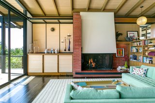 Each corner of the home is thoughtfully laid out with little wasted space. Beamed ceilings, built-in shelving, and a brick fireplace add to the living room's character.