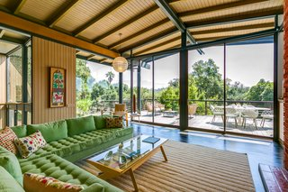 A striking wall of glass looks out over the treetops, while deep overhangs provide additional privacy and shade for the interior space. Sliding doors lead out to a sunny deck.