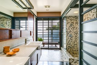 Elements of the modern master bathroom mimic the post-and-beam style. The warm wood vanity and earth-hued tiles complement the home's original character.