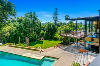 Dense foliage surrounds the residence—the current homeowners say it's like living in a treehouse. Views from the upper deck extend to the San Gabriel Mountains.