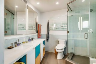One of three bathrooms, the updated master bath features the same plywood and maple cabinetry as in the kitchen. Colorful accents and modern features complement the space.