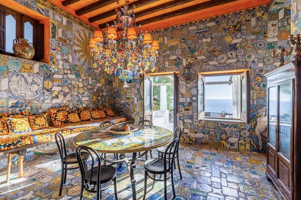A breakfast area overlooks the terrace and views of the sea. A stunning mosaic of hand-painted majolica tiles canvases the floor and walls, contrasting with custom designed fabrics along the built-in couch.