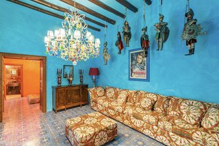 The formal sitting area is painted in a striking shade of sky blue. Antiques line the walls and hang from the timber-beamed ceilings, while a different majolica tile motif covers the floor.