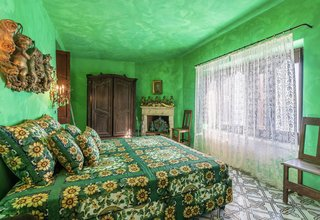 Lace curtains line the large windows of this emerald green suite, which also features an antique fireplace and furnishings.