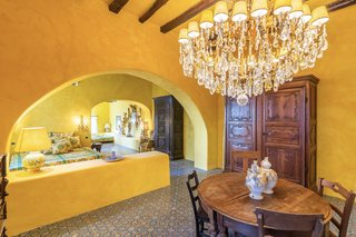Several guest bedrooms are larger for extended stays. Here, a three-room suite painted in a golden yellow features arched openings and a plastered half wall to separate the spaces.