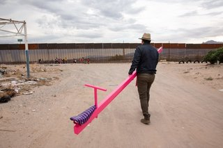 Ronald Rael heads towards the border carrying one half of the three pink teeter-totters.