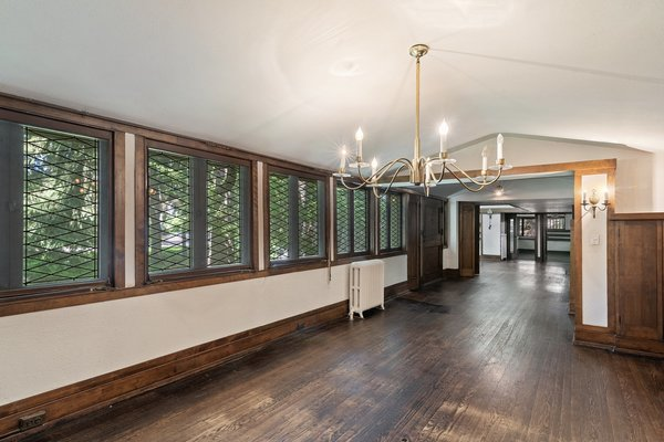 A 22-foot long dining area is revealed once through the entry way. Diamond leaded glass windows run along the wall, complemented by wooden trim and a pitched ceiling.