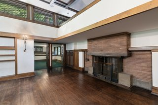At the opposite end of the living room is a large brick fireplace, with a balcony overlooking the space from a second-story loft. Double glass doors open up to a window-wrapped sun porch.