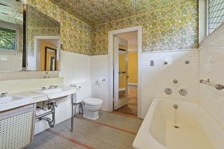 One of three full bathrooms, the spacious area offers a soaking tub and access to the bedroom. A large window brings natural light into the space.