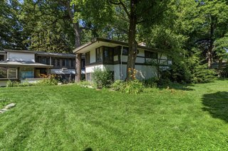 The large backyard offers a grassy area and plenty of mature trees. According to conservation reports, the home was affectionately referred to as the 'Baker Bungalow' by local residents.