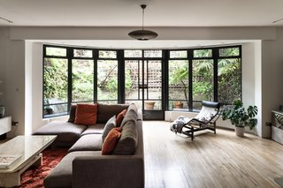An expansive bay window is a dramatic centerpiece, framing views of a lush backyard garden. The metal glasswork lends a greenhouse-like atmosphere to the space.
