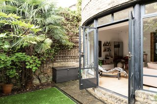 French doors open to a private oasis. The curvaceous rear facade contrasts with the home's linear, symmetrical front.