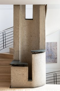 Beech wood floors continue up the spiral staircase. A hollowed-out concrete column rises through the home's three levels, adding a sculptural point of interest to each story.