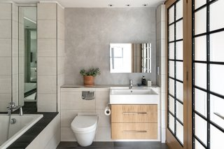 The master bathroom offers a soaking tub and a modern vanity. A wall of frosted glass doors bring natural light into the space while also providing access to the hallway.