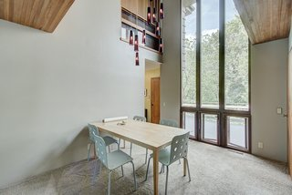 Natural light pours into the formal dining space from 18-foot-tall windows. Rising up toward the cathedral ceiling, the windows frame views of the property's many trees.