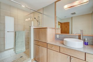 A modern master bathroom can be found off of the bedroom, complete with a large vanity and tiled shower.