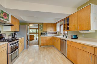 The large kitchen offers cabinetry galore and modern appliances. Light hardwood floors complement the neutral color palette.