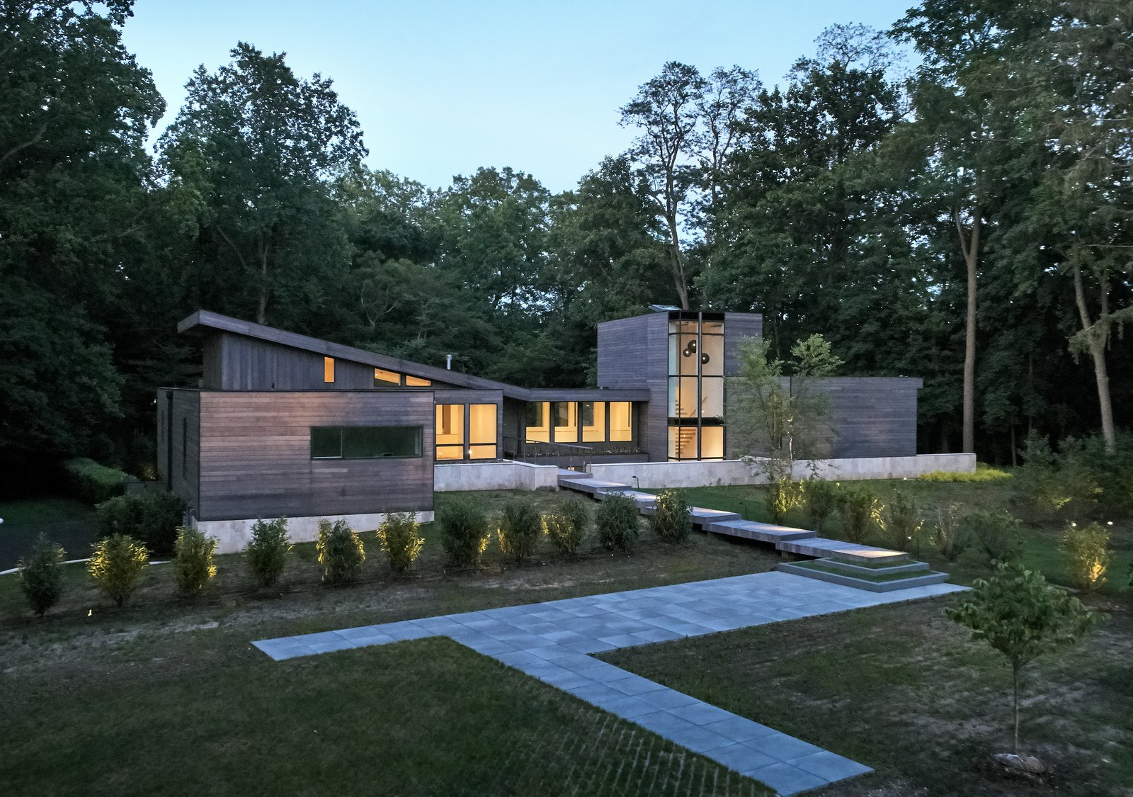 Exterior, Butterfly, Shingles, Wood, Hipped, Metal, Glass, House, and Flat At first glance, the structure appears to be a single-story home. The surrounding trees create additional privacy as the yard begins to slope toward the rear.  Exterior Glass Butterfly Metal House Photos from Walls of Windows Connect a Home With Earth and Sky