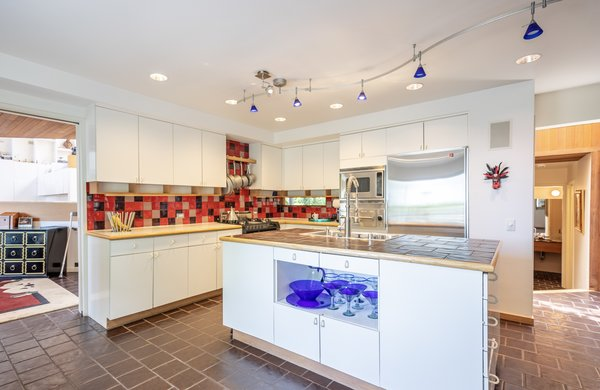 In the open kitchen, a bold red backsplash delightfully contrasts with the crisp white cabinetry.