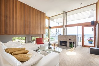 The richly textured tongue-and-groove paneling continues into the multi-leveled living room, which looks out onto views of the lake. A cozy conversation pit surrounds the fireplace hearth.