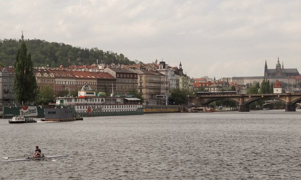 An image of the home during its journey down the Vltava River with the iconic Charles Bridge and Prague Cathedral in the background. A custom steel pontoon was built for the prefabricated structure, the two joined together at a shipyard 25 miles north of Prague.