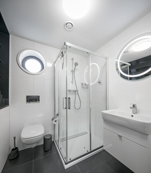 The full bathroom offers enough space and storage, with a porthole window above the loo.