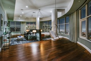 The expansive bedroom features dark hardwood floors that contrast with the crisp, white ceiling and columns. Darker hues of green, blue, and gray add to the palette.