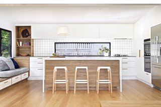 A spacious new kitchen is at the heart of the expanded living space. Centered with the island, a long horizontal window trimmed in black contrasts the crisp white palette.