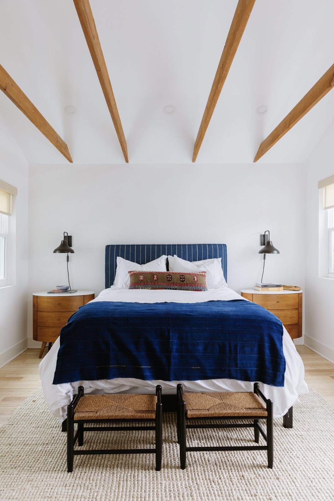 Bedroom, Night Stands, Light Hardwood Floor, Bed, Bench, and Wall Lighting Wooden beams delicately span a gabled ceiling in the guest bedroom.  Photos from A Young Couple Revamp Adam Levine's Childhood Home
