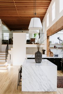 A soaring, wood-beamed atrium is an unexpected surprise upon entering the home. The renovated kitchen features a large marble island that visually grounds the space.