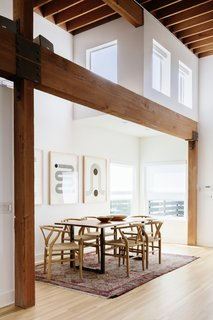 A dining nook is framed by timber beams running above the space. The sunny corner is illuminated by an additional grouping of clerestory windows.