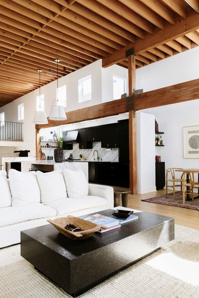 The living room, kitchen, and dining room flow together in the open floor plan. Previously, the kitchen featured darker wooden cabinets in a more traditional style.