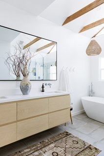 In the renovated master bathroom the couple opted for a natural wood vanity to complement the beams overhead. A cool white color palette creates a serene atmosphere.