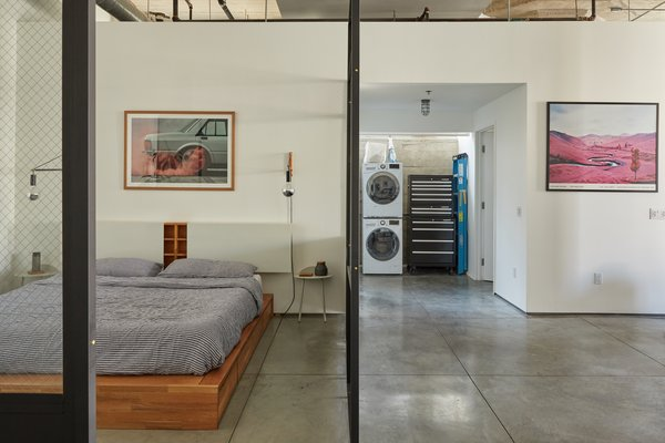 The spacious bedroom is neatly tucked behind glass walls, offering a quiet place of refuge. In the distance, stackable laundry units and storage separate the bath from the walk-in closet.