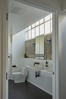 The newly remodeled bathroom features a sleek black-and-white color palette, with Duravit wall-mounted sinks basking in the filtered light of clerestory windows.