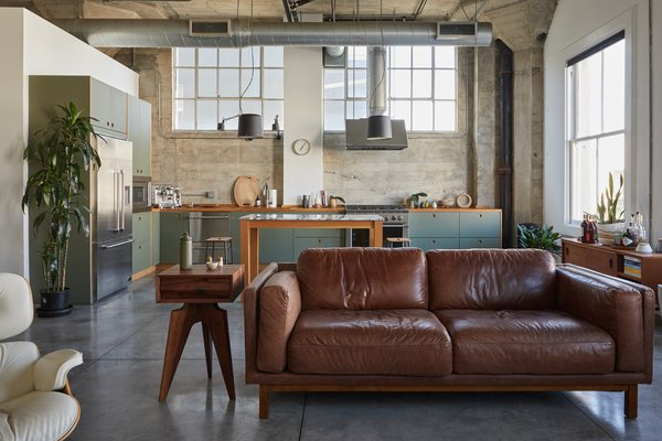 The loft's original open floor plan, 13-foot-tall ceilings, and polished concrete floors remain. A modern, streamlined kitchen is now a central focal point.