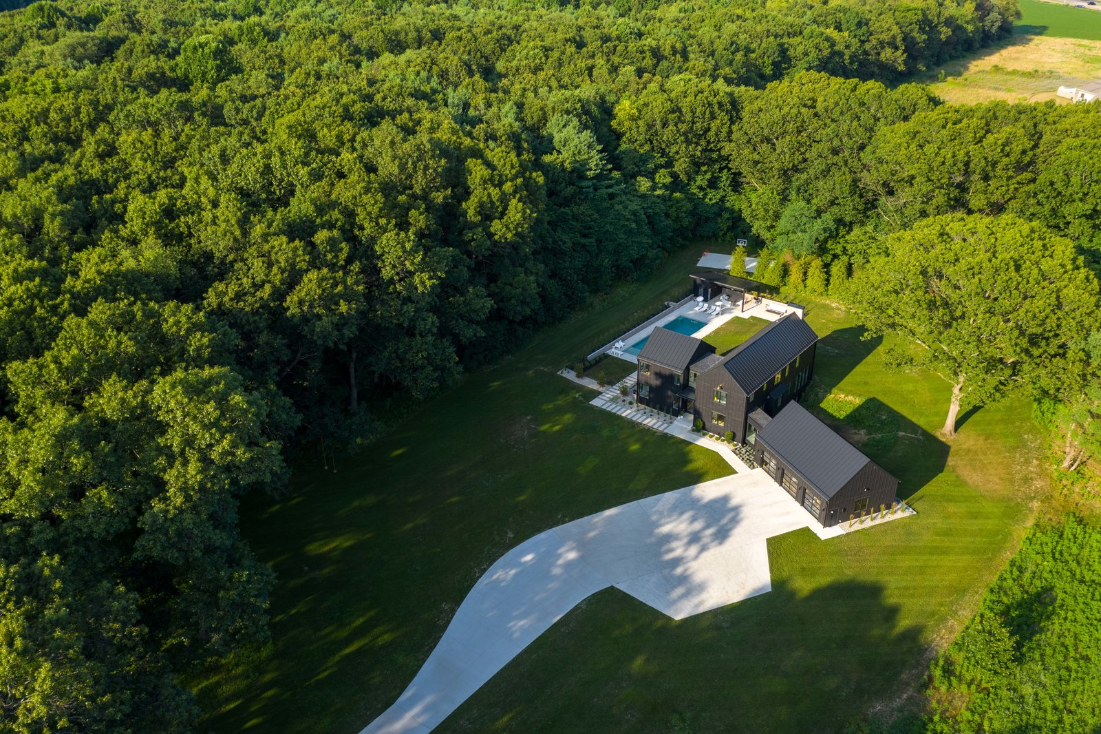 Exterior, A-Frame RoofLine, Metal Roof Material, and House Building Type An aerial shot of the property showing the house nestled in a clearing. The dense wooded surroundings inspired the couple to prioritize exterior views in the home's design  Photo 3 of 10 in Watch How This Danish-Style Farmhouse Unites a Family With Nature