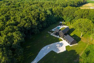 An aerial shot of the property showing the house nestled in a clearing. The dense wooded surroundings inspired the couple to prioritize exterior views in the home's design