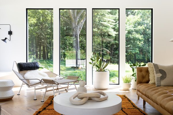 Throughout the home, large picture windows frame views of the greenery outside, including glimpses of a 150-year-old oak tree the couple worked hard to save.